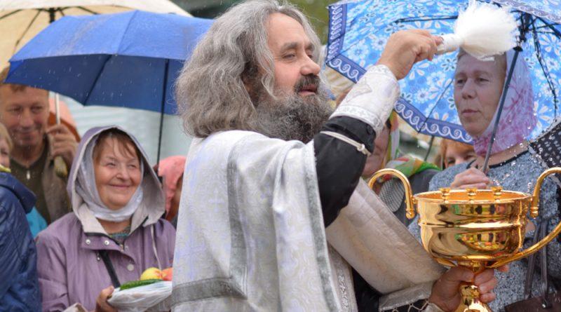 Отец Михаил окропляет святой водой присутствующих.